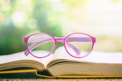 Eyeglasses помещенные на раскрытой книге против запачканного естественного gree Стоковые Фотографии RF