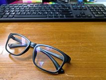 Eyeglasses устанавливают на старом деревянном столе с запачканным keyboa компьютера стоковое изображение