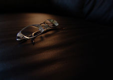 Eyeglasses. A pair of eyeglasses on a black leather sofa Royalty Free Stock Image