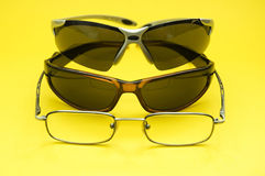 Eyeglasses. Different kind of eyeglasses isolated on yellow stock images
