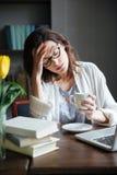 Утомленная вымотанная зрелая женщина в eyeglasses полагаясь на ее руке стоковые фото