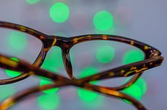 Blur vision. Eyeglasses against bokeh Christmas lights background. Vision or business concept Royalty Free Stock Photos