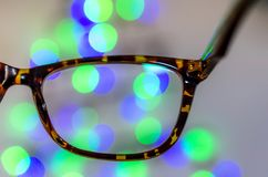 Vision concept glasses. Eyeglasses against bokeh Christmas lights background. Vision or business concept Stock Photo