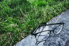 Eyeglasses in black rim liying on the granite surface near the grass stock images