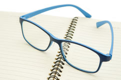 Eyeglasses on a blank paper notepad. Stock Photo