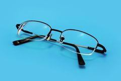 Eyeglasses on Blue. Eyeglasses on a blue background with smooth shadow Stock Photo