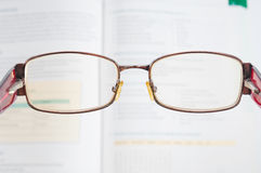 Eyeglasses and blurred textbook Royalty Free Stock Photography