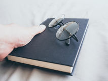Eyeglasses and book in bedroom for reading and relax. stock photography