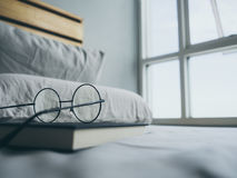 Eyeglasses and book in bedroom for reading and relax. stock images