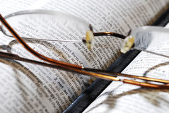 Eyeglasses, book and pencil. Closeup photo of book and reading glasses with pencil Stock Photos