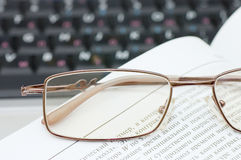 Eyeglasses and books on the laptop Stock Photo