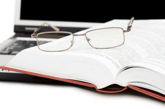 Eyeglasses and books on the laptop Royalty Free Stock Image