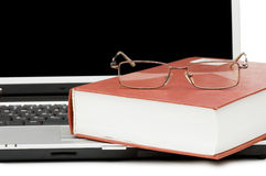 Eyeglasses and books on the laptop Stock Photos