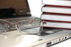 Eyeglasses and books on laptop