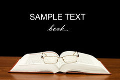Eyeglasses on books on a wooden table Stock Photo
