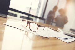 Eyeglasses, business document and laptop computer notebook on wo. Oden table with people background, selective focus and vintage tone Stock Images
