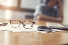 Eyeglasses, business document and laptop computer notebook on wo. Oden table, selective focus and vintage tone Royalty Free Stock Photography