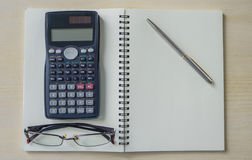 Eyeglasses,calculator and silver pen on spiral notebook Royalty Free Stock Photography