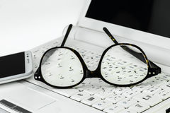 Eyeglasses  and cell phone on a small laptop Stock Photo