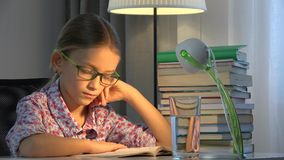 Eyeglasses child reading book, girl studying at desk lamp, learning children 4K stock video footage