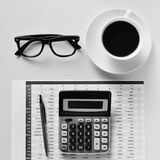 Eyeglasses, coffee and calculator on an office desk Royalty Free Stock Photo