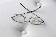 Eyeglasses with cracked lens on cream colored ottoman Royalty Free Stock Images