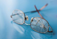 Eyeglasses with cracked lens on shiny blue background Royalty Free Stock Images