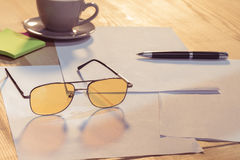 Eyeglasses, cup of coffee, sticky notes, blank papers and pen on table. Close-up view of eyeglasses, cup of coffee, sticky notes, blank papers and pen on table Stock Photo