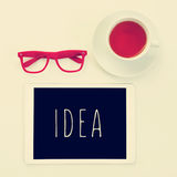 Eyeglasses, cup of tea and word idea in a tablet computer Royalty Free Stock Photography