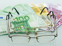 Eyeglasses and currencies Royalty Free Stock Photography