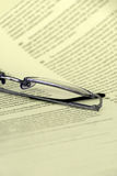 Eyeglasses on a document closeup. Reading and education concept Stock Photography