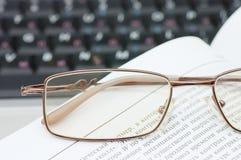 Eyeglasses e livros no portátil foto de stock