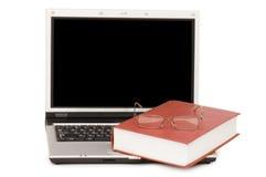 Eyeglasses e livros no portátil imagem de stock