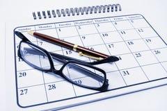 Eyeglasses e pena no calendário imagens de stock royalty free