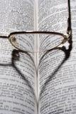 Eyeglasses em um livro imagem de stock royalty free