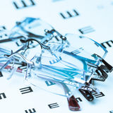 Eyeglasses on eye chart Royalty Free Stock Images