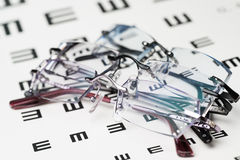Eyeglasses on eye chart Stock Photography