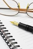 Eyeglasses and fountain pen on notebook Stock Images