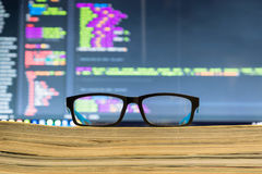 Eyeglasses in front off computer screen with Code syntax Royalty Free Stock Images