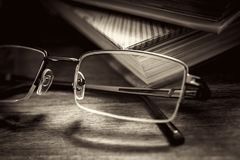 Eyeglasses In Front Of Some Books On Wooden Table In Vintage Monochrome Colors. Eyeglasses In Front Of Some Books On A Wooden Table In Vintage Monochrome Colors royalty free stock photos