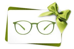Eyeglasses gift card, green spectacles and green ribbon bow, iso stock image