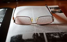Eyeglasses With Gold-colored Frame on Opened Book Stock Images