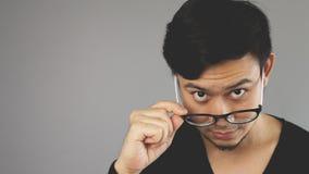 An eyeglasses guy looking at camera. An asian man with black t-shirt royalty free stock photos
