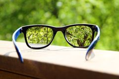 Eyeglasses in the hand over blurred background Stock Photos
