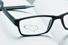 Eyeglasses and heart drawn in a notebook, in duotone Stock Photos