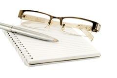 Eyeglasses i pióro na książce fotografia stock