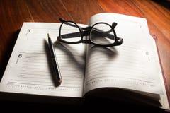 Eyeglasses i pióro na plan książce Zdjęcia Royalty Free