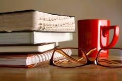 Eyeglasses, kawowy kubek i stos książki, obrazy stock