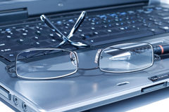 Eyeglasses on lap top. PC concept with lap top, pen and eyeglasses royalty free stock photos