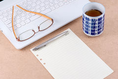 Eyeglasses on laptop with a cup of tea. And a pen on paper note Stock Images